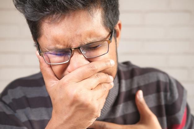 Jovem asiático tossindo e espirrando de perto