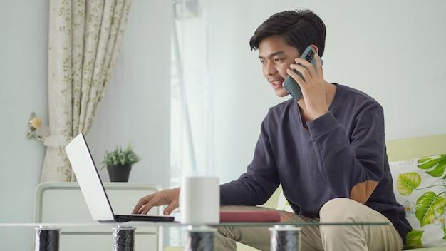 Jovem asiático trabalhando em casa ao telefone