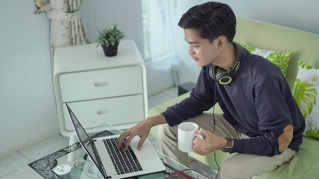 Jovem asiático trabalhando em casa usando seu laptop com um copo de bebida