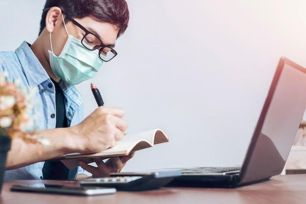Jovem asiático usa máscara para proteger vírus trabalhando com laptop em casa