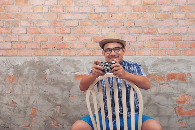 Jovem asiático usa uma câmera no estúdio