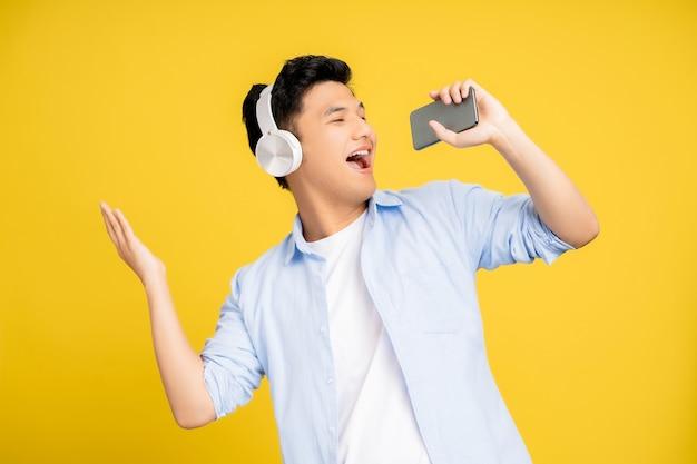 Jovem asiático usando fones de ouvido e cantando favorito em um fundo amarelo do estúdio. ele está muito feliz.