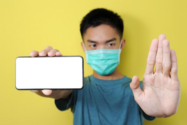 Jovem asiático usando máscara de proteção, fazendo gesto de parar para impedir, compartilhar boato, notícias falsas, isolado no amarelo