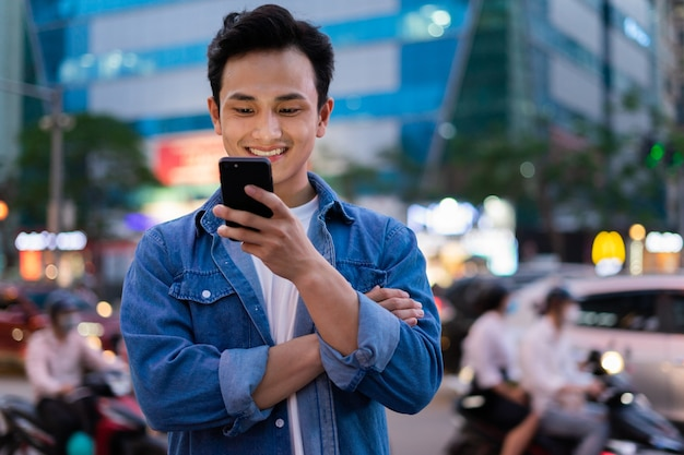 Jovem asiático usando smartphone na rua à noite