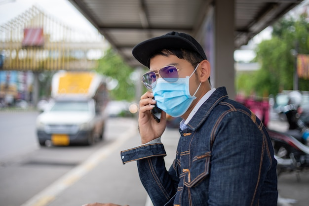 Jovem asiático usando telefone inteligente na cidade e usando máscara facial para proteção da poluição do ar, partículas e proteção contra vírus da gripe, influenza, coronavírus