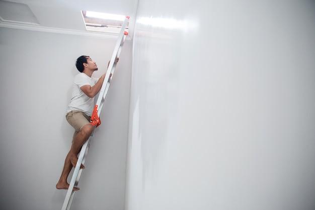 Jovem asiático usando uma escada para consertar o teto quebrado em casa