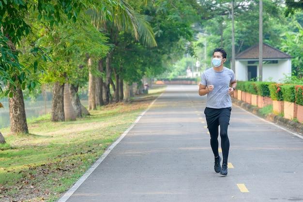 Jovem asiático use uma máscara de fitness corra no parque suor de um conceito de treino matinal: use uma máscara contra sars-cov-2.