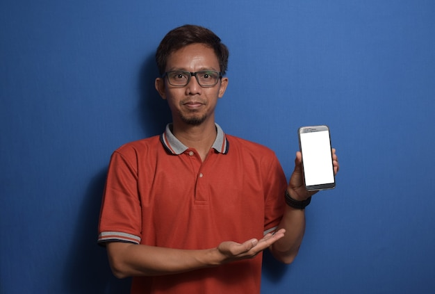 Jovem asiático vestindo camiseta laranja casual e óculos, mostrando a tela do smartphone em branco