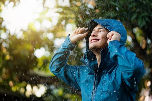 Jovem asiático vestindo capas de chuva ao ar livre.