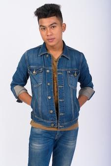 Jovem asiático vestindo jaqueta jeans contra uma parede branca