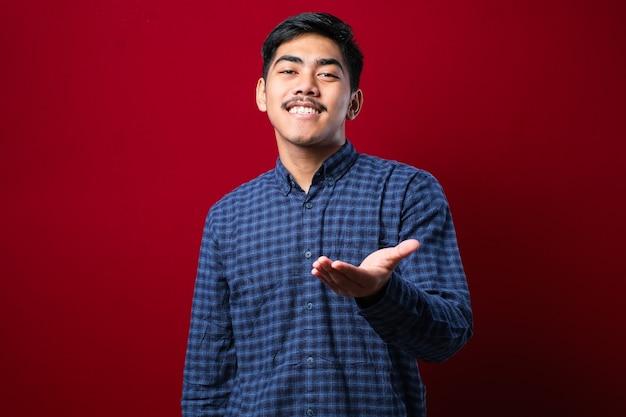Jovem asiático vestindo roupas casuais, sorrindo amigável oferecendo um aperto de mão como saudação e boas-vindas sobre fundo vermelho. negócio de sucesso.