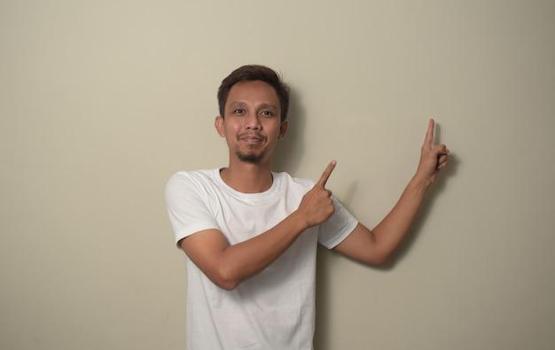 Jovem asiático vestindo uma camiseta branca, sorrindo e apontando com as duas mãos e dedos para o lado