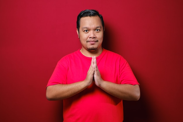Jovem asiático vestindo uma camiseta vermelha com um gesto de saudação e boas-vindas, isolado no fundo vermelho