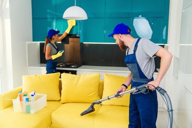 Jovem aspira sofá amarelo e linda garota limpando móveis de cozinha. produtos de limpeza profissionais em apartamento.