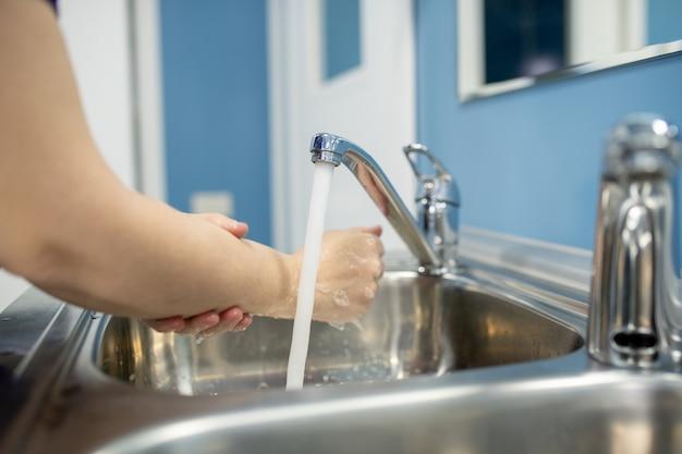 Jovem assistente, enfermeira ou cirurgiã lavando as mãos sobre uma das duas pias metálicas antes ou depois de um procedimento médico no hospital