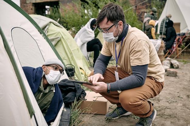 Jovem assistente social com distintivo agachada na barraca e fazendo anotações no tablet enquanto fala com refugiado