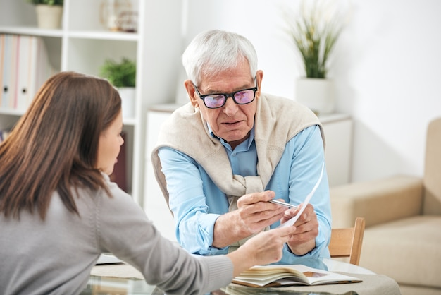 Jovem assistente social ou agente de seguros fazendo perguntas a um homem sênior sobre pontos do papel durante uma consulta domiciliar