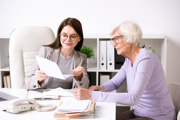 Jovem assistente social sorridente, sentada à mesa com uma senhora sênior e explicando o conteúdo do documento para ela