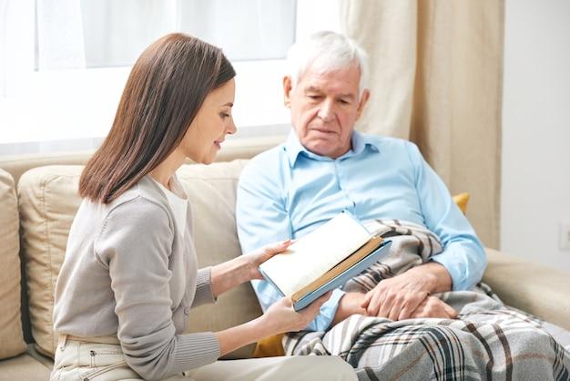 Jovem assistente social sorridente, sentada no sofá, lendo um livro para um homem idoso debaixo do cobertor