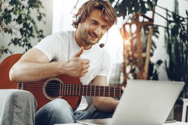 Jovem assistindo a um tutorial de guitarra em seu laptop