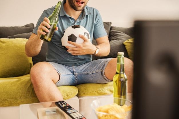 Jovem assistindo futebol na tv e bebendo cerveja em casa