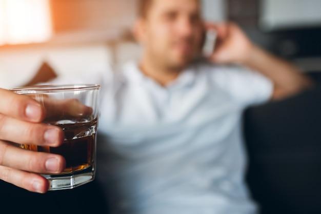 Jovem assistindo tv em seu próprio apartamento. cara, falando no telefone e segurando o copo de álcool na mão.