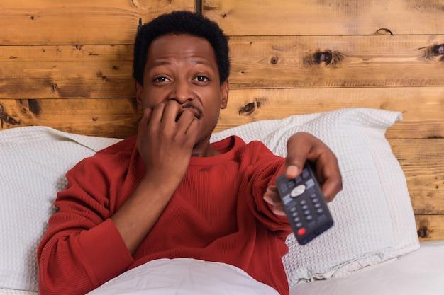 Jovem assistindo tv na cama em casa.