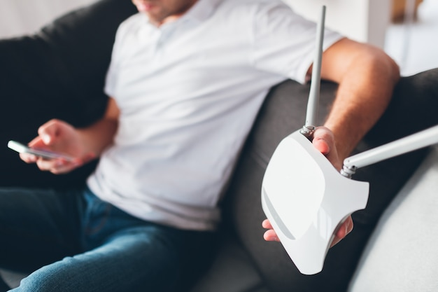 Jovem assistir tv em seu próprio apartamento. corte a vista do cara segurando o roteador wi0fi na mão. personalizando-o. tente ligar usando telefone celular ou smartphone. o dispositivo precisa de reparo.