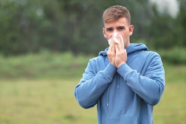 Jovem assoando o nariz com um lenço