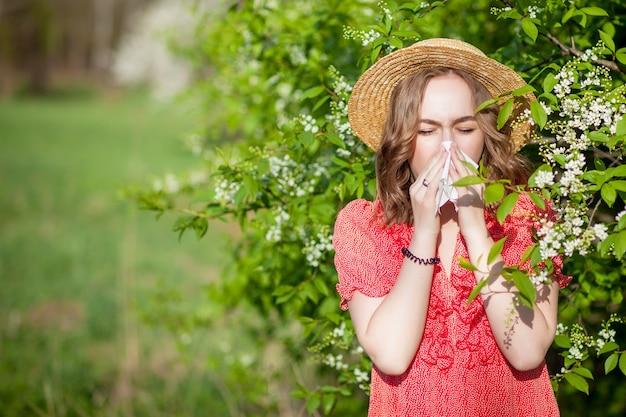 Jovem assoando o nariz e espirrando em um lenço de papel na frente de uma árvore em flor