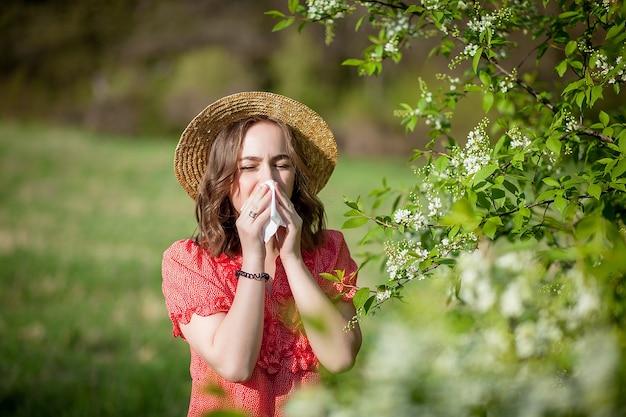 Jovem assoando o nariz e espirrando em um lenço de papel na frente de uma árvore florescendo. alergênicos sazonais que afetam as pessoas. bela dama tem rinite.