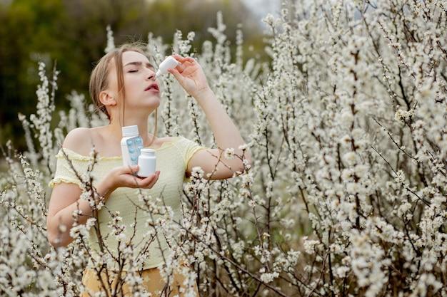 Jovem, assoando o nariz e espirrando em um lenço de papel na frente de uma árvore florescendo. alergênicos sazonais que afetam as pessoas. bela dama tem rinite.