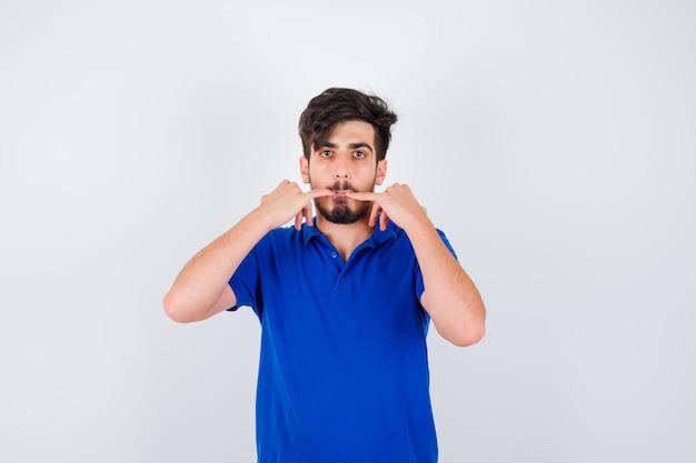 Jovem assobiando de camiseta azul e parecendo sério