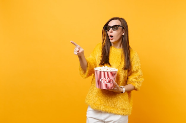 Jovem assustada chocada em óculos 3d imax apontando o dedo indicador, assistindo filme filme, balde de pipoca isolado no fundo amarelo brilhante. emoções sinceras de pessoas no conceito de estilo de vida de cinema.