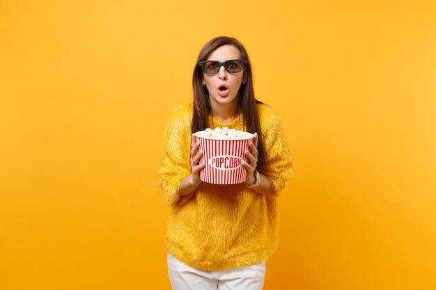 Jovem assustada chocada em óculos 3d imax, assistindo a um filme, segurando um balde de pipoca isolado em um fundo amarelo brilhante. emoções sinceras de pessoas no conceito de estilo de vida de cinema. área de publicidade.