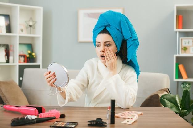 Jovem assustada colocando a mão na bochecha segurando e olhando para o espelho enrolado em uma toalha, sentada à mesa com ferramentas de maquiagem na sala de estar