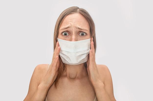 Jovem assustada e assustada parece. ela segura a máscara com as duas mãos. modelo está doente.