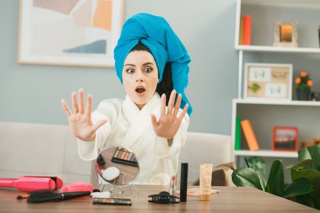 Jovem assustada enrolando o cabelo em toalha de unhas de gel secas, sentada à mesa com ferramentas de maquiagem na sala de estar