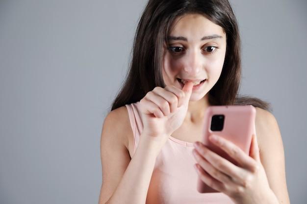 Jovem assustada segurando um smartphone rosa