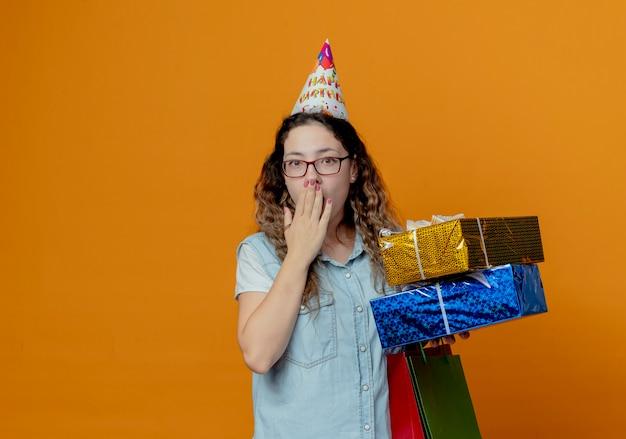 Jovem assustada usando óculos e boné de aniversário segurando caixas de presente com sacolas de presente