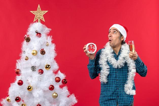 Jovem assustado com chapéu de papai noel, segurando uma taça de vinho e um relógio em pé perto da árvore de natal no vermelho