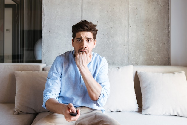 Jovem assustado segurando o controle remoto da tv