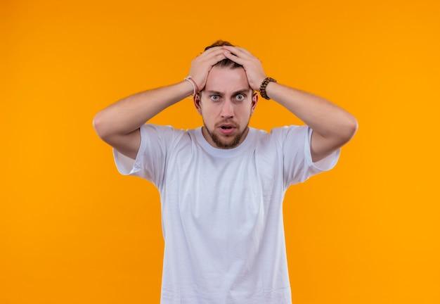 Jovem assustado vestindo camiseta branca segurando a cabeça em um fundo laranja isolado