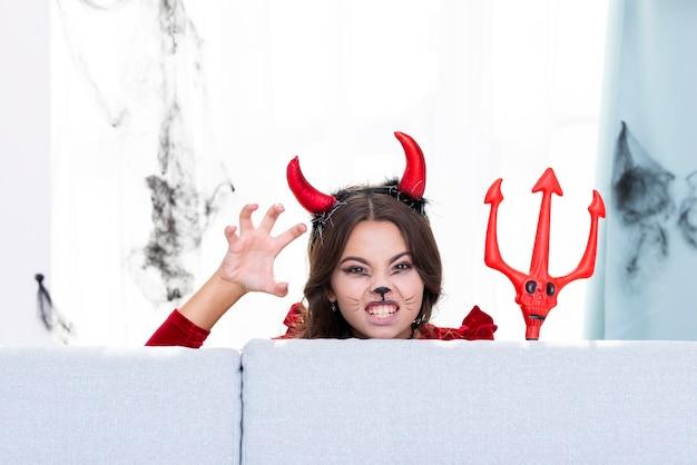 Jovem assustadora com chifres de diabo e tridente