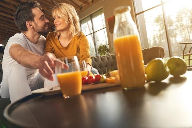 Jovem atencioso pegando um copo de suco de laranja para sua linda esposa caucasiana