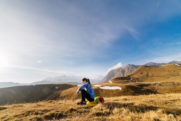 Jovem ativa com um paletó azul viaja ao longo da cordilheira do cáucaso com uma mochila e uma barraca