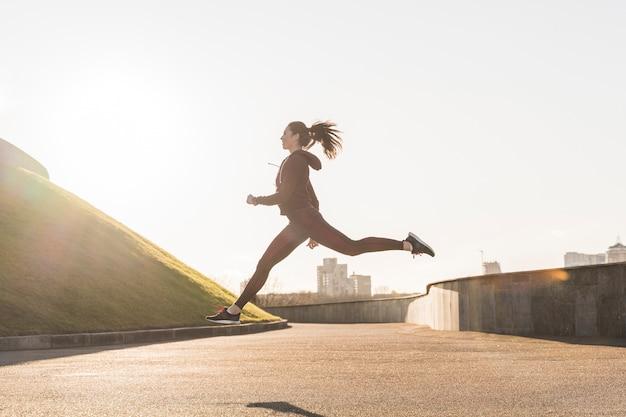 Jovem ativa correndo ao ar livre