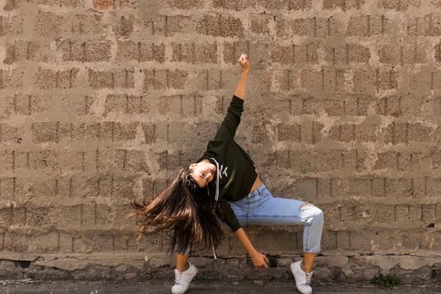 Jovem ativa dançando contra a parede velha