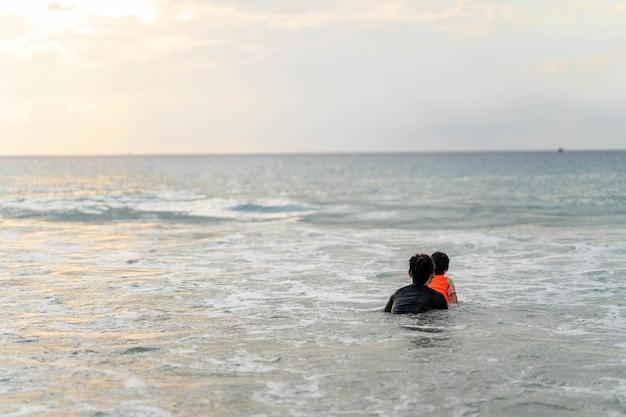 Jovem ativa mãe e filha em maiô brincando na praia contra o pôr do sol no mar.