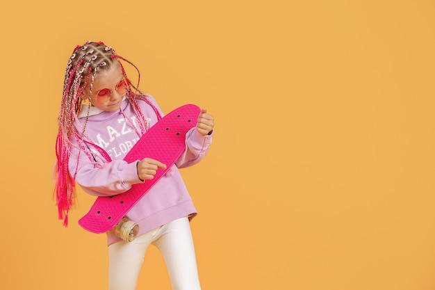 Jovem ativa na camisa rosa e calção branco, segurando o skate sobre fundo amarelo